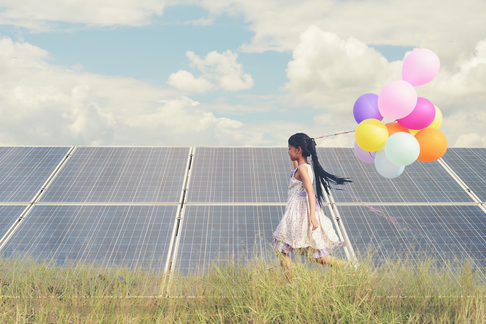 Kleines Mädchen läuft über die Wiese in der Hand bunte Luftballons im Hintergrund Solarpannels