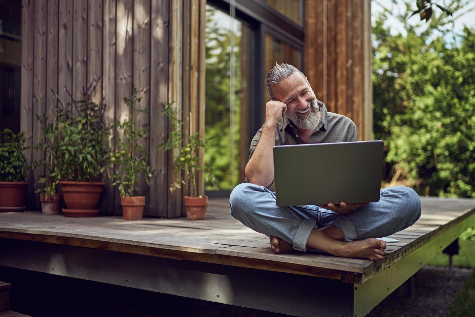 Mann mit Bart sitzt barfuß auf einer Veranda vor Holzhaus Laptop auf dem Schoß