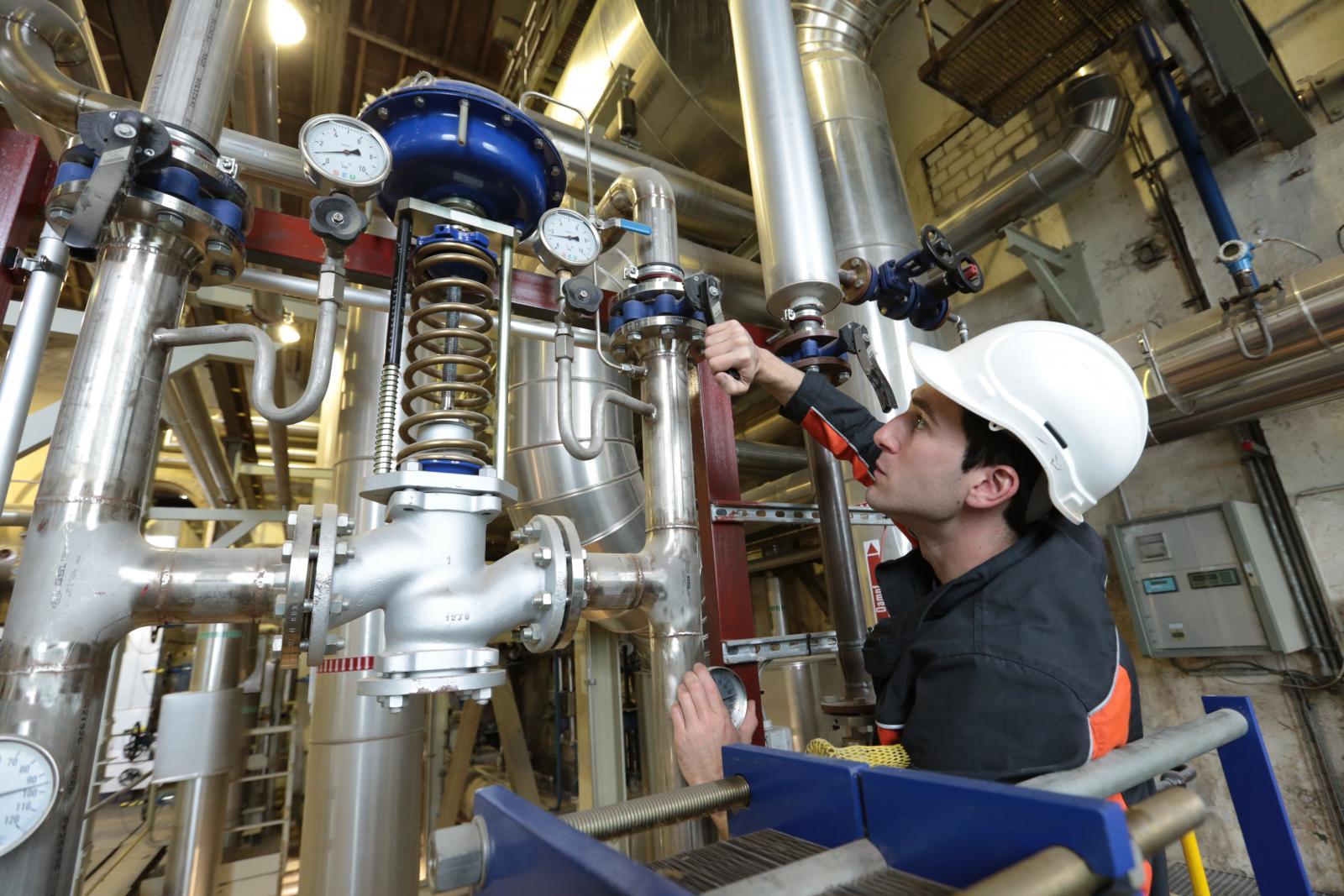 Mann mit Schutzhelm beim überprüfen von Rohrleitungen