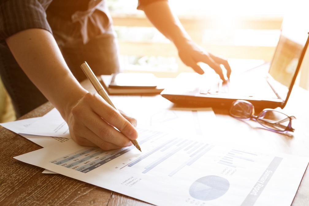 Frau mit Stift rechts über Papierunterlagen und am Laptop links bei der Arbeit