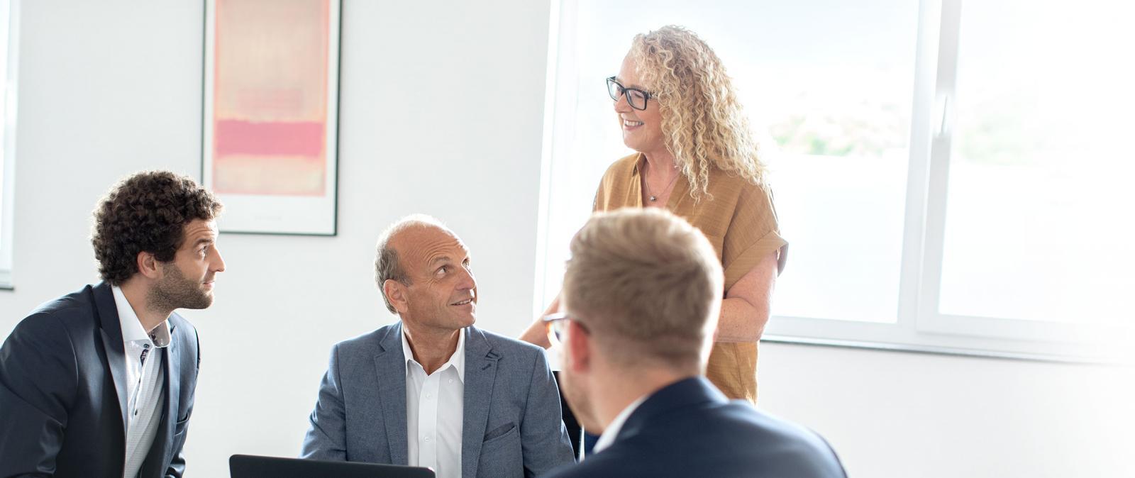 Eine Frau und drei Männer in Besprechungssituation