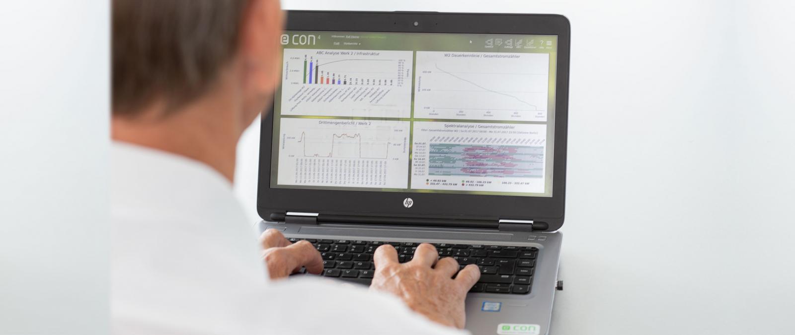 Mann vor Laptop econ Software auf Laptopscreen