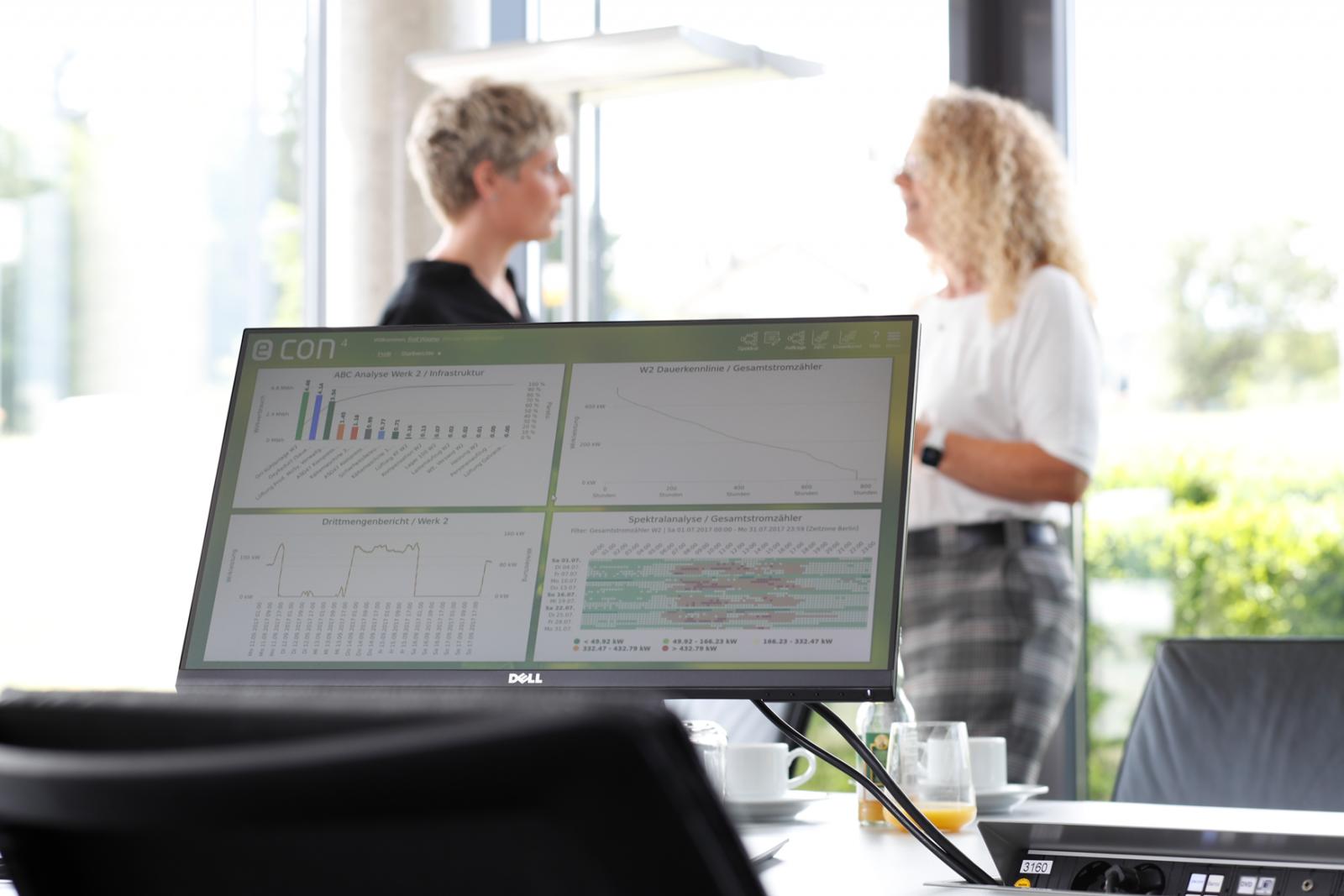 Softwarescreen, im Hintergrund zwei Frauen im Gespräch