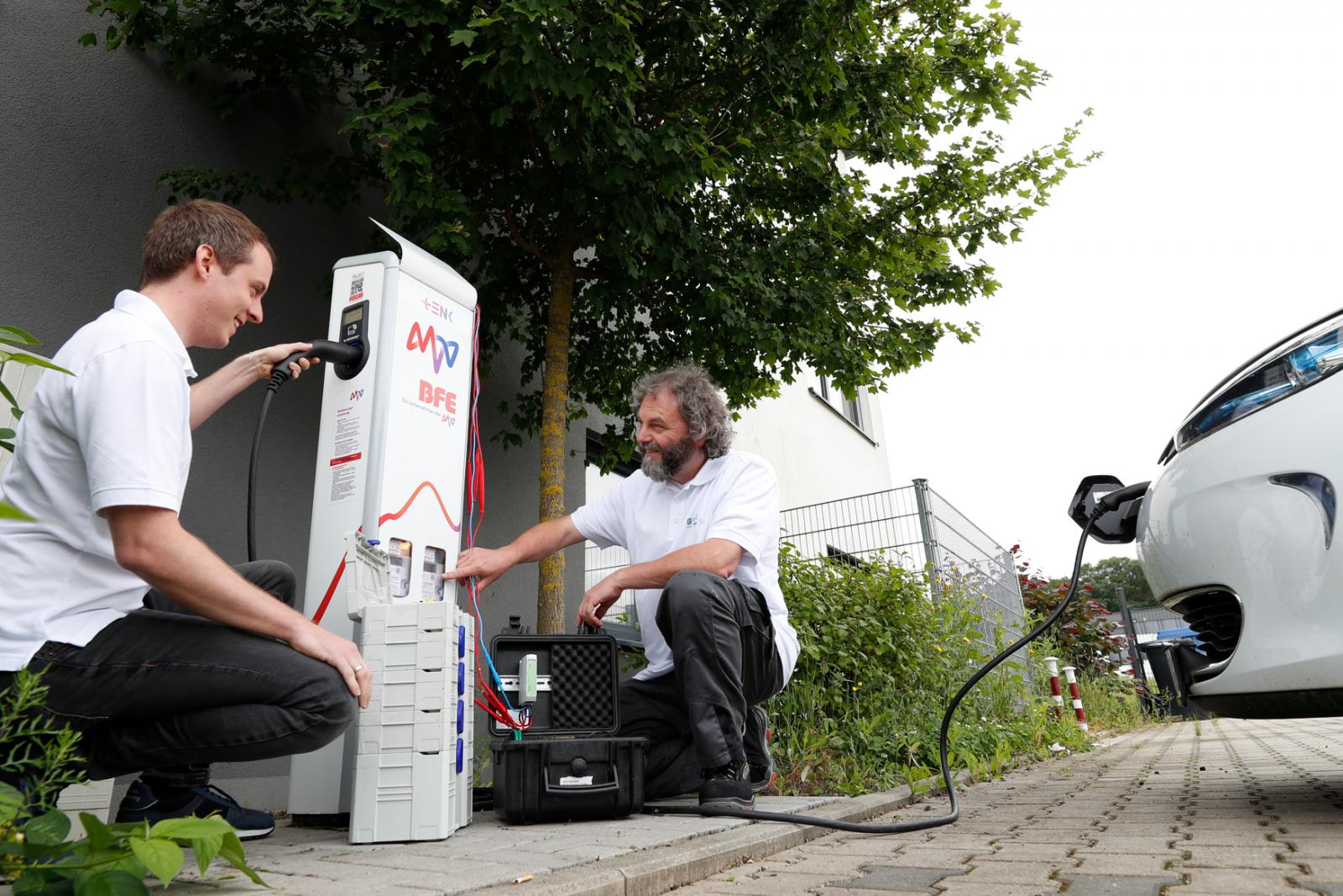 Zwei Techniker an der Ladesäule, Ladestecker im E-Auto
