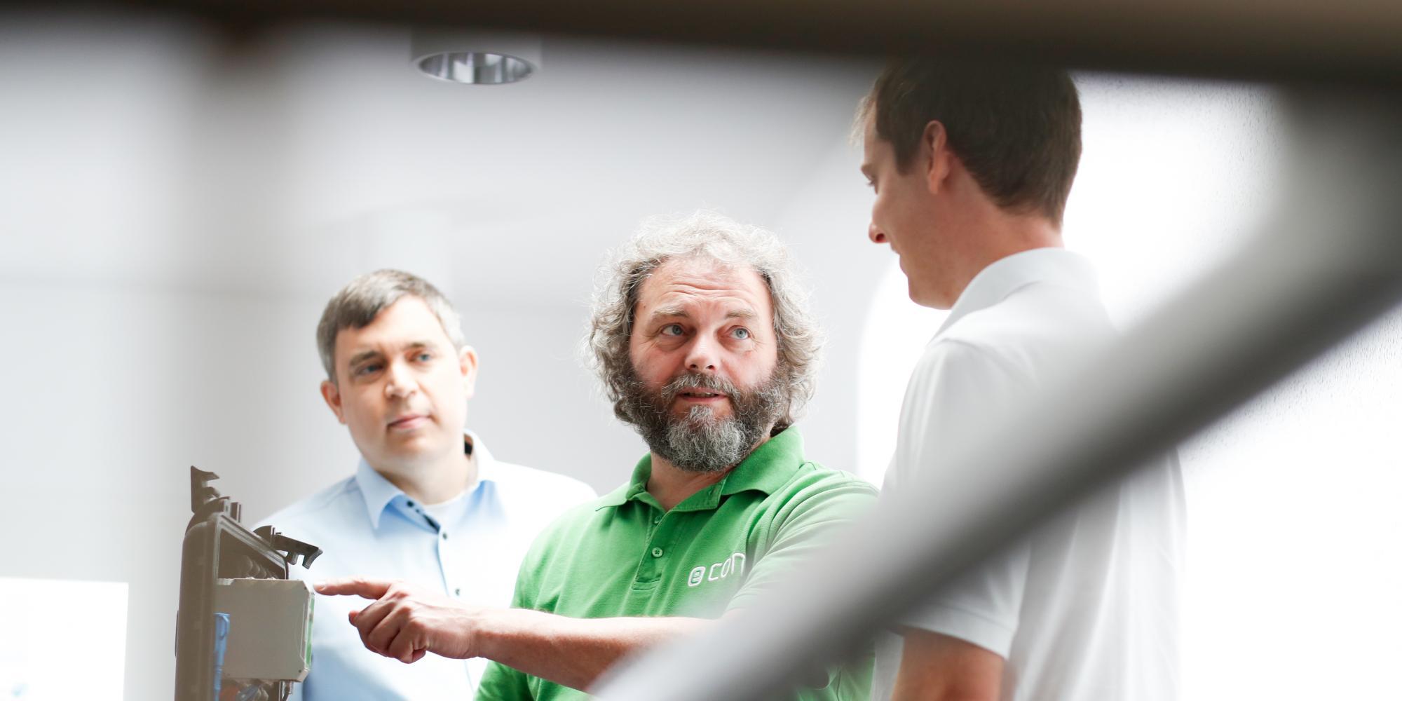 Techniker in Besprechung mit zwei Männern dabei ein Messkoffer