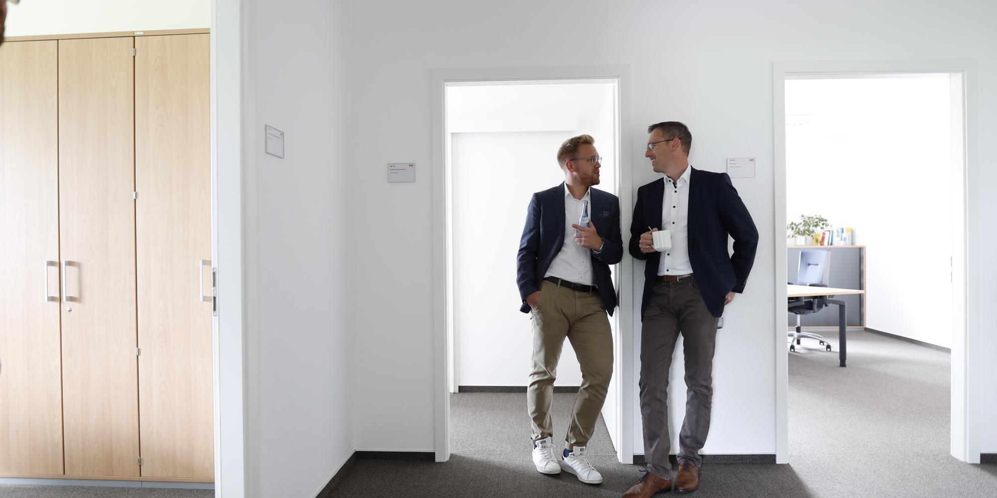 Zwei Männer unterhalten sich lässig am Türrahmen angelehnt im Büroflur