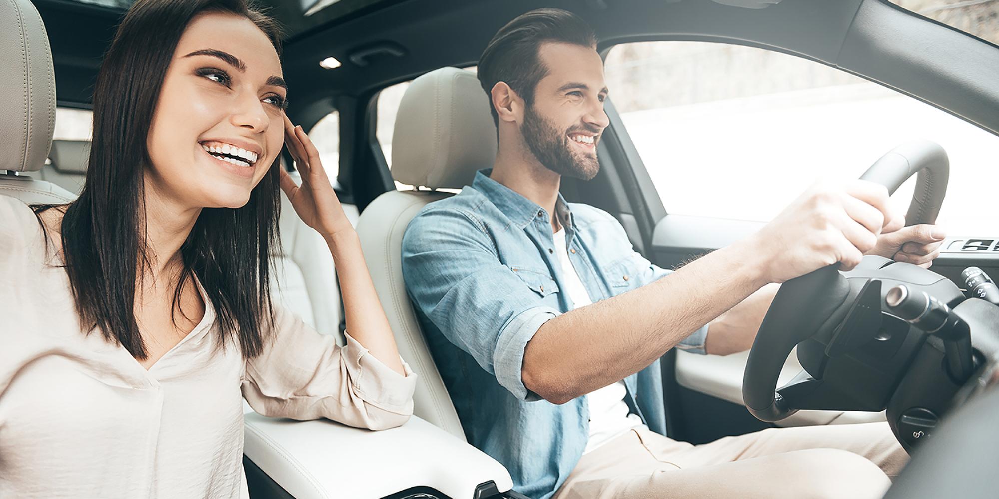 Junge lächelnde Frau und junger lächelnder Mann im Auto