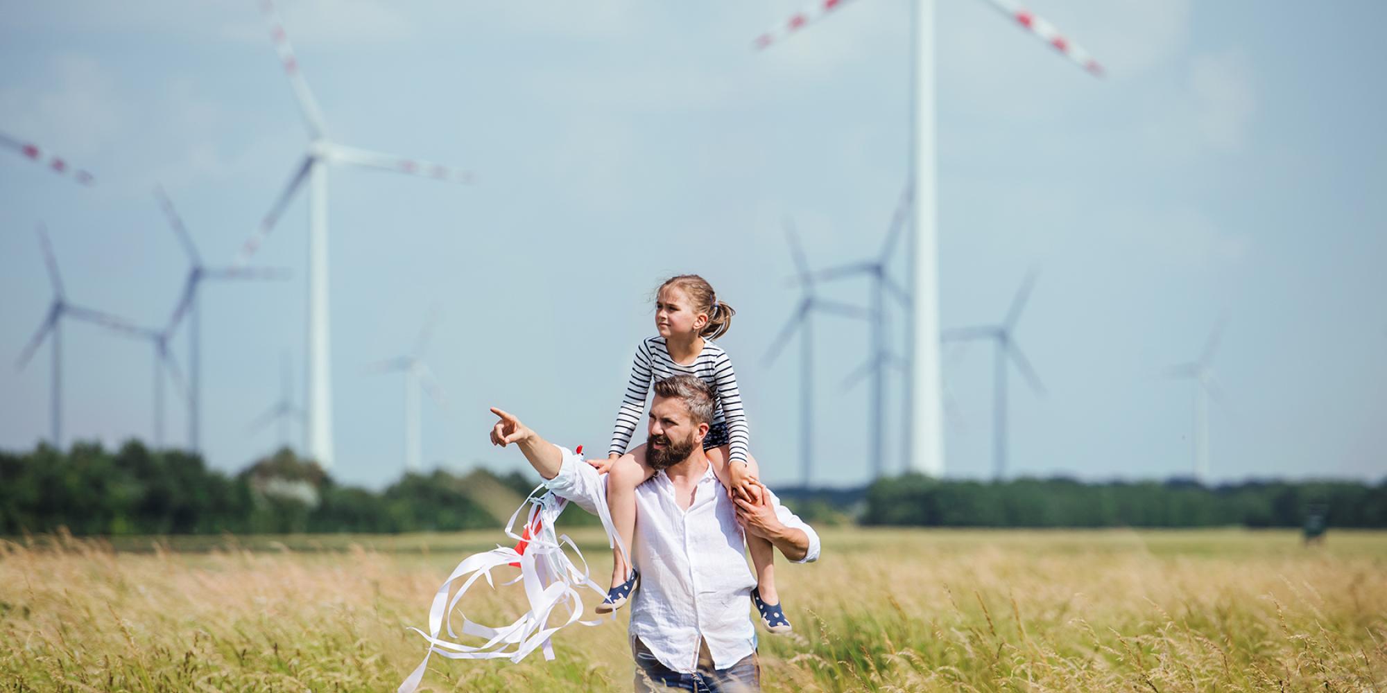 Papa hat seine kleine Tochter auf der Schulter im Feld im Hintergrund Windräder
