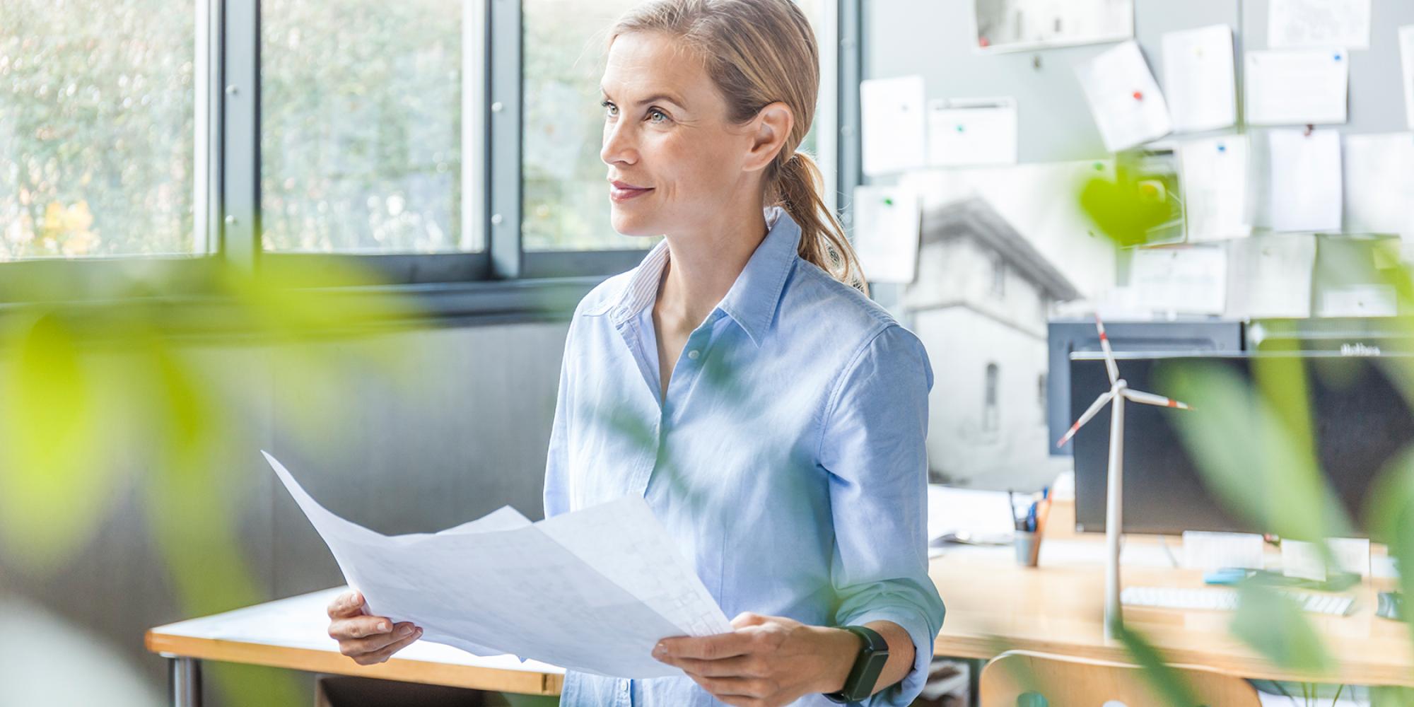 Frau im Büro hält Unterlagen in der Hand
