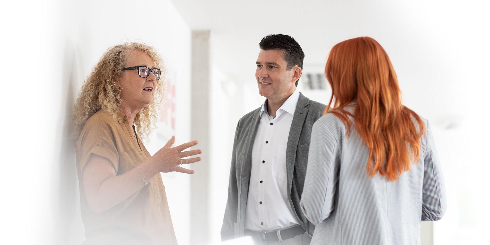 Zwei Frauen und ein Mann unterhalten sich