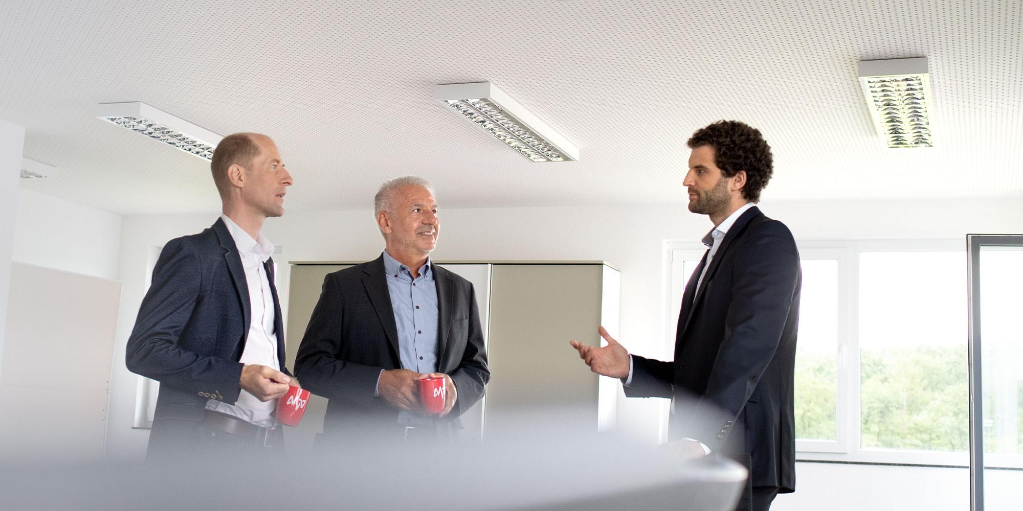 Drei Männer stehen im Besprechungsraum und unterhalten sich
