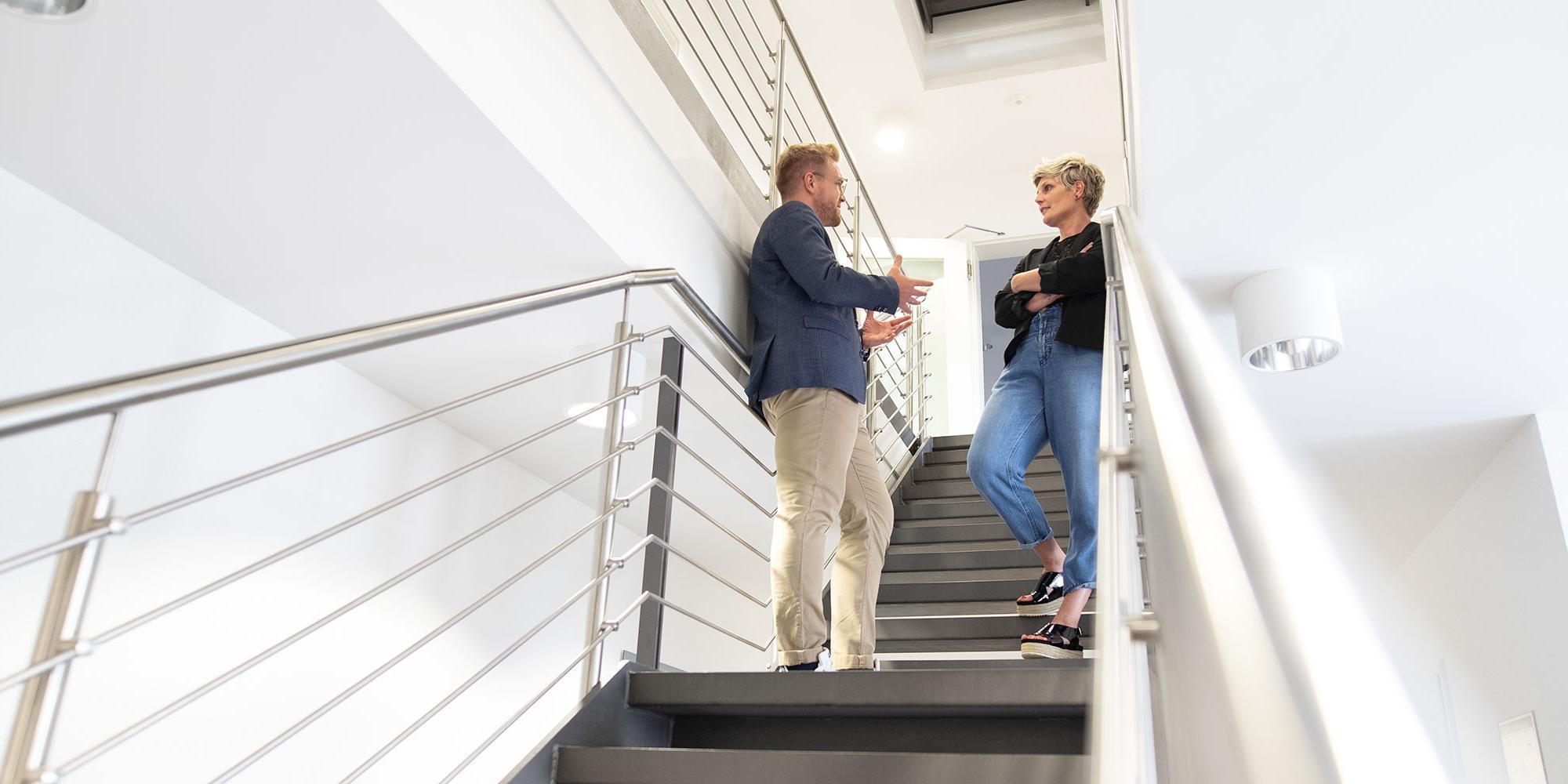 Eine Frau und ein Mann unterhalten sich im Treppenhaus