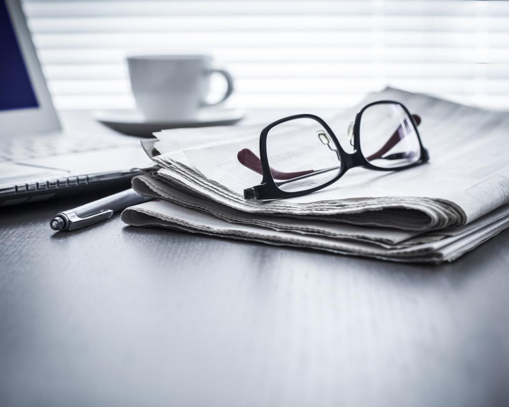 Brille auf Zeitung vor Laptop neben Stift und Kaffeetasse