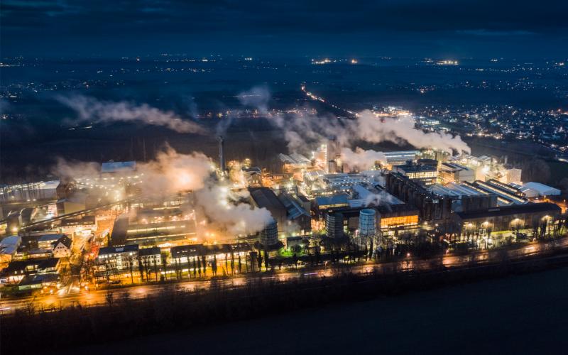 Blick auf beleuchtete Stadt in Dunkelheit man sieht die Rauchwolken der Fabriken