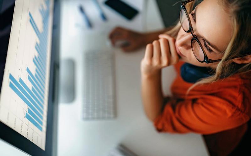 Frau mit Brille sitzt vor Computermonitor darauf zu sehen Diagramme
