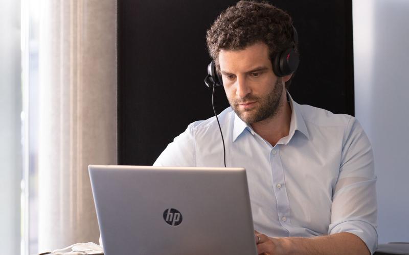 Junger Mann mit Headset vor Laptop