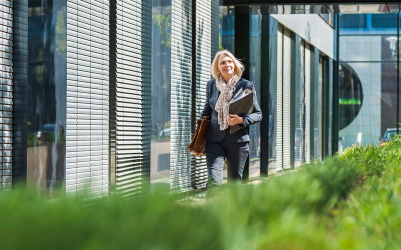 Geschäftsfrau vor Bürogebäude, Grünanlage